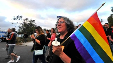 People carried signs and flags as they marched down University Avenue in Hillcrest. Photo by Chris Stone
