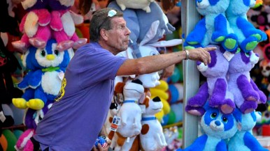 A game booth worker beckons players in the Fun Zone at the San Diego County Fair. Photo by Chris Stone