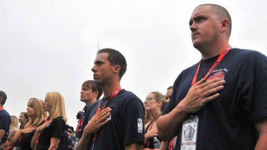 Firefighters put their hands on their hearts during the national anthem. Photo by Chris Stone