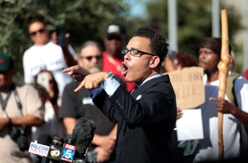 Rev. Shane Harris speaks to protesters gathered at the El Cajon Police Department headquarters to protest fatal shooting of an unarmed black man Tuesday by officers in El Cajon. REUTERS/Earnie Grafton