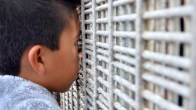 A young boy peeks through a small opening in the fence to see people in Mexico. Photo by Chris Stone