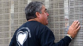 Enrique Morones, founder and director of Border Angels, speaks with Mexican citizens through a border fence. Photo by Chris Stone