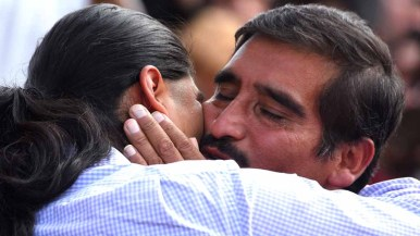 Eduardo Hernandez shares a quiet moment with his son, Luis, after the border fence is opened. Photo by Chris Stone
