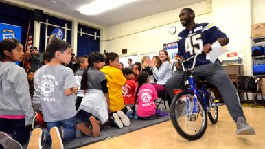 Chargers player Asante Cleveland rides in on one of the bikes to be given to a child. Photo by Chris Stone