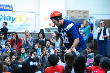 Chargers player Hunter Henry is greeted by pupils at Baker Elementary School. Photo by Chris Stone