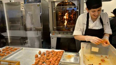 An employee of OceanView Terrace dining hall prepares kosher meatballs, while chicken cooks in the rotisserie behind her. Photo by Chris Stone