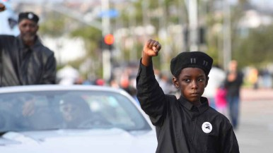 A young man marches with the Black Panthers in the the annual Martin Luther King Parade. Photo by Chris Stone