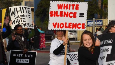 Member of San Diego Showing up for Racial Justice group carried signs promoting their issues. Photo by Chris Stone
