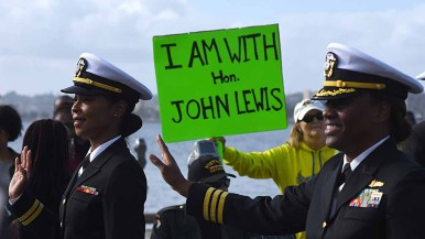 A spectator holds a sign showing her support for Rep. John Lewis D-Ga., who called Donald Trump an illegitimate president. Photo by Chris Stone
