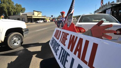 Supporters of Duncan Hunter and President Donald Trump put up signs on Main Street in Ramona. Photo by Chris Stone