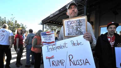 A protester holds signs while waiting in line to get into the Town Hall meeting. Photo by Chris Stone