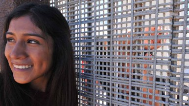 Hayde Lorenzo, 17, visits with her mother, Reynea Mosso, through the border fence. Photo by Chris Stone