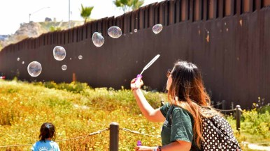 A woman makes bubbles as children enjoy gifts from Border Angels for International Children's Day. Photo by Chris Stone