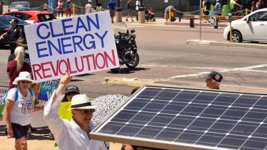 Apt sign passes by solar panel for bike ride station during People's Climate March San Diego. Photo by Ken Stone