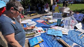 People's Climate March San Diego visitor scans signs before rally at Waterfront Park. Photo by Ken Stone
