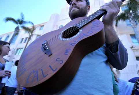 """Marshall Voit led a choir at People's Climate March San Diego, strumming a guitar labeled """"The Machine Calls for Revolution."""" Photo by Ken Stone"""