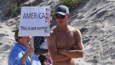 A beachgoer checked out the anti-Trump protest outside the Hotel del Coronado. Photo by Chris Stone