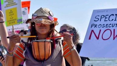 A protester with a small drum beats to the rhythm of the chants. Photo by Chris Stone