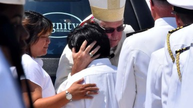 Most Rev. John Dolan, auxiliary bishop, comforts brother Luke Sibayan as his mother, Carmen, consoles her son. Photo by Chris Stone