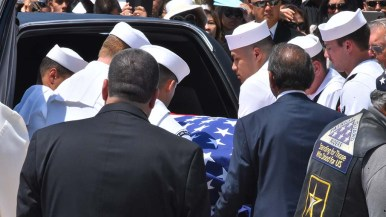Navy pallbearers place the coffin of Carlos Sibayan into a hearse after the funeral. Photo by Chris Stone