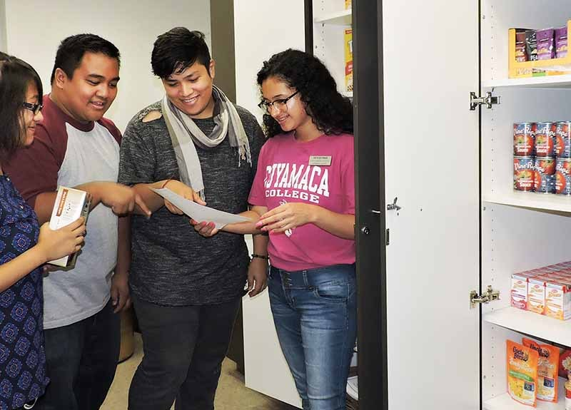 From left, Cuyamaca College students Kyrie Macogay, Eduardo Mangosing , Jesus Suarez and Iveth Estrada help stock the shelves of the campus food pantry. The students are all active in student government.