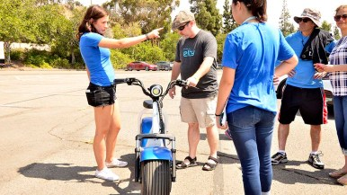 Electric Vehicle Day attendees check out the Phat electric scooters.