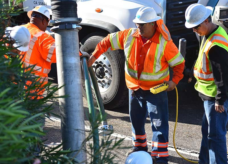 Caltrans workers repair a water main break on eastbound Interstate 8 in Mission Valley.