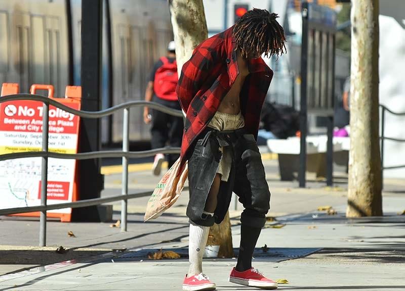 A homeless man dances on a sidewalk in downtown San Diego.