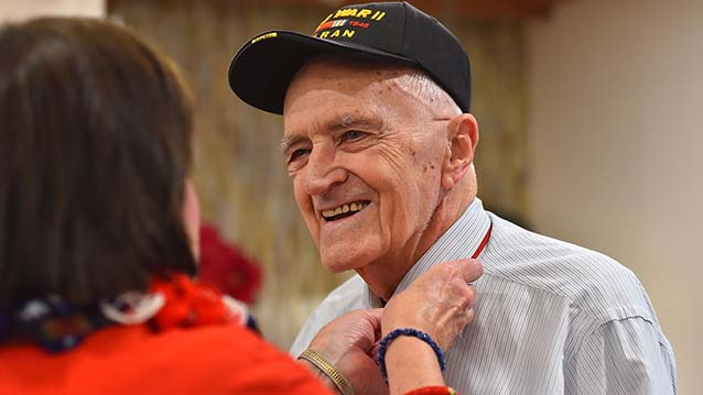 World War II Navy veteran Robert Doyle receives a pin honoring his military service.