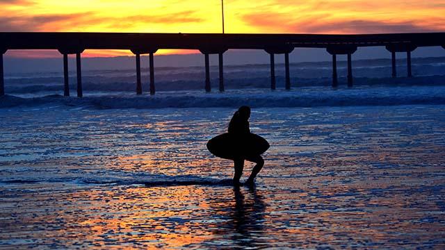 A woman with a skim board walks across the beach of Ocean Beach pier.