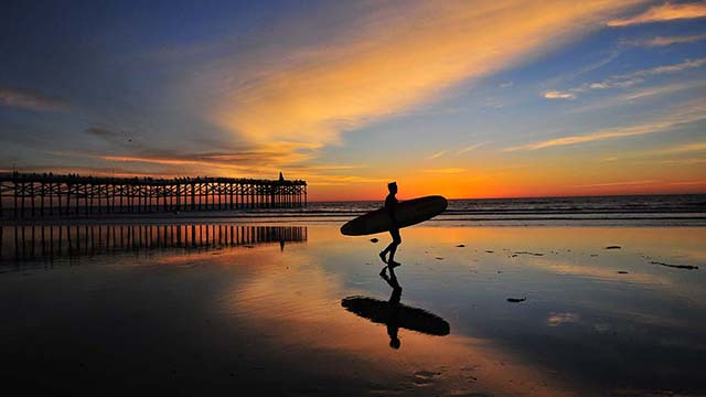 A surfer leaves the waves at sunset near Crystal Pier in Pacific Beach.
