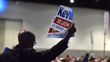 A volunteer hands out campaign signs for U.S. Senate candidate Kevin de Leon.