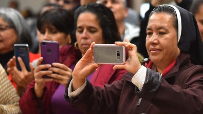 Parishioners line up to get photos of Fr. Richard Brown at his farewell party at Our Lady of Guadalupe Church.
