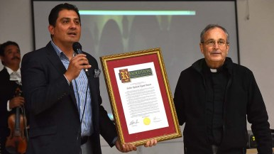State Sen. Ben Hueso along with the Rev. John Auther, S.J. show the Rev. Richard Brown a state legislature resolution in his name.