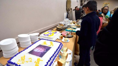 Parishioners line up for desserts including a cake with Fr. Brown's portrait on it.