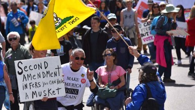 A marcher has words with a counter-protestor holding a Don't Tread on Me flag.