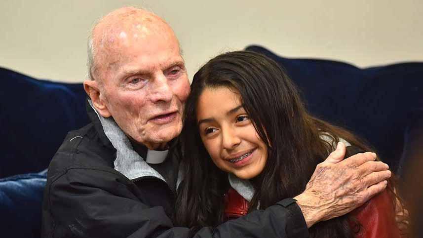 The Rev. Richard Brown hugs Anahi Balladares, 12, at the farewell dinner for him.
