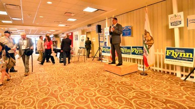 Sean Flynn, Republican congressional candidate from the 31st district, speaks as delegates pass by.