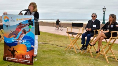 Councilwoman Lorie Zapf welcomes visitors to Mission Beach as cyclist passes by. Photo by Ken Stone