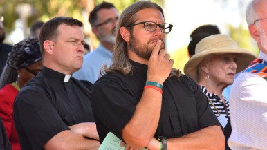 The Rev. Kyle Baker, SJ, of Los Angeles listens to testimonials of DACA recipients. Photo by Chris Stone