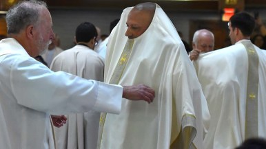 Elias Puentes, who was born in Mexico, gets help with his vestments during the ordination.