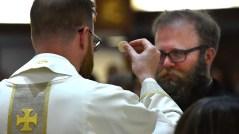 Newly ordained Jesuit priest John Tillman Tanner distributes communion to a parishioner.