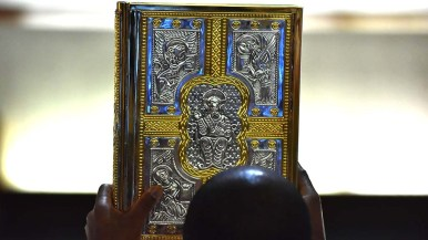 A liturgical book is taken to the altar during the ordination.