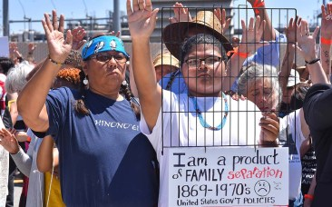 Members of the native American community join in the prayers in front of the detention center.