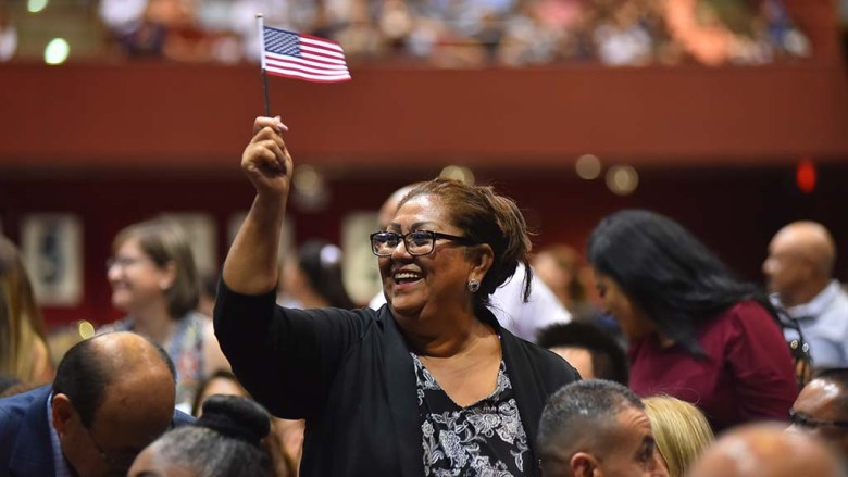 An immigrant waves a flag during a naturalization ceremony