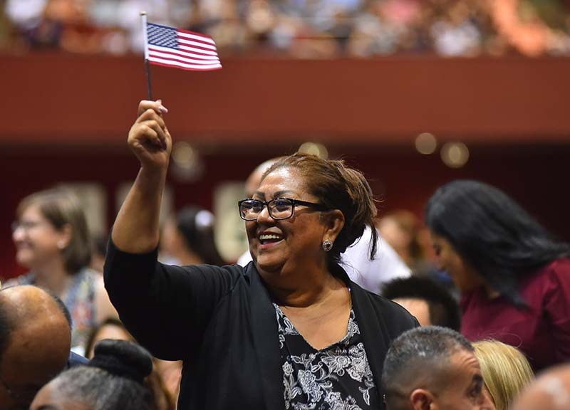 The immigrants, from 75 countries, stood and waved their American flags as the judge recognized their countries of origin.