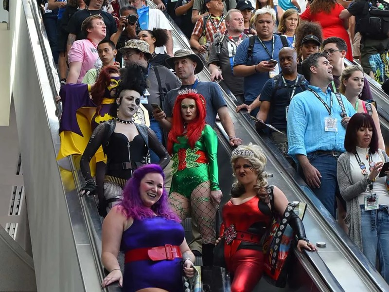 Comic-Con attendees, some cosplayers, descend the escalator in the convention center.