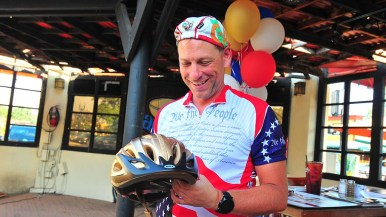 Mark Meuser, Republican candidate for state attorney general, is gifted a gold colored bike helmet.