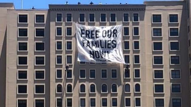 """Banner saying 'FREE OUR FAMILIES NOW"""" was hanged from near top of Westin Gaslamp Hotel."""