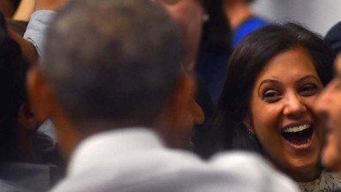 An excited audience member reaches out to shake hands with Barack Obama.